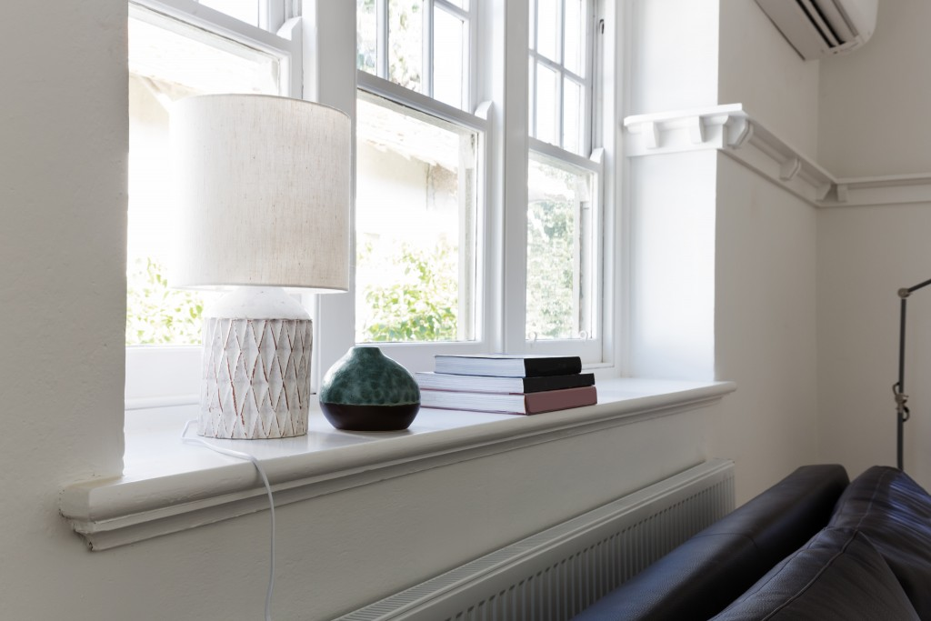 Close up details of lamp books and ornament objects on a white window sill